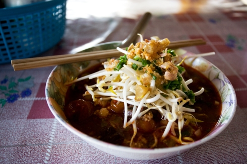 Here's noodle with nam nieuw topped with fried pork rinds, bean sprouts and green onions.